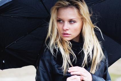 Jeune femme blonde sous la pluie avec un parapluie